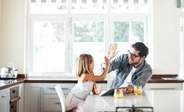 Man and child high five in kitchen